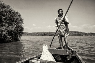 Boat man on a nearby lake with a temple on an island